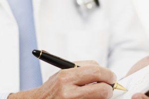 Physician Writing Prescription --- Image by © Sean Justice/Corbis